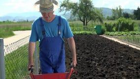 Άτομο με το καπέλο που καλλιεργεί το μέσο πυροβολισμό εδάφους απόθεμα βίντεο