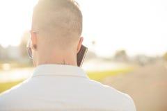 Άτομο με το κινητό τηλέφωνο στα χέρια, πίσω άποψη, υπαίθρια Στοκ Εικόνες