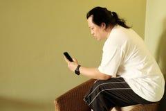 Άτομο με το μακρυμάλλες smartphone ανάγνωσης και χρησιμοποίησης Στοκ φωτογραφία με δικαίωμα ελεύθερης χρήσης