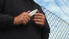 Άτομο με το μαχαίρι κοντά στο φράκτη απόθεμα βίντεο