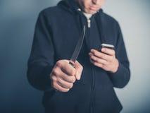 Άτομο με το μαχαίρι που χρησιμοποιεί το smartphone Στοκ φωτογραφίες με δικαίωμα ελεύθερης χρήσης