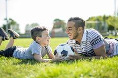 Άτομο με το παίζοντας ποδόσφαιρο παιδιών στον τομέα Στοκ εικόνες με δικαίωμα ελεύθερης χρήσης