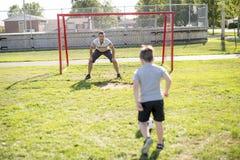 Άτομο με το παίζοντας ποδόσφαιρο παιδιών στον τομέα Στοκ Εικόνα