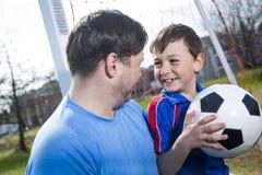 Άτομο με το παίζοντας ποδόσφαιρο παιδιών στην πίσσα Στοκ Εικόνα