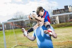 Άτομο με το παίζοντας ποδόσφαιρο παιδιών στην πίσσα Στοκ φωτογραφία με δικαίωμα ελεύθερης χρήσης