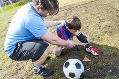 Άτομο με το παίζοντας ποδόσφαιρο παιδιών στην πίσσα Στοκ Φωτογραφίες