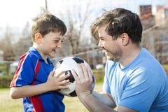 Άτομο με το παίζοντας ποδόσφαιρο παιδιών στην πίσσα Στοκ εικόνα με δικαίωμα ελεύθερης χρήσης