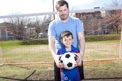 Άτομο με το παίζοντας ποδόσφαιρο παιδιών στην πίσσα Στοκ Φωτογραφία