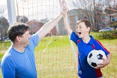 Άτομο με το παίζοντας ποδόσφαιρο παιδιών στην πίσσα Στοκ Εικόνες