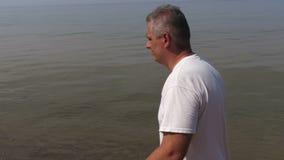 Άτομο με το περπάτημα των πόλων στη θάλασσα απόθεμα βίντεο