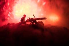 Άτομο με το πολυβόλο τη νύχτα, το υπόβαθρο έκρηξης πυρκαγιάς ή τις στρατιωτικές σκιαγραφίες που παλεύει τη σκηνή στο υπόβαθρο ουρ Στοκ Φωτογραφία