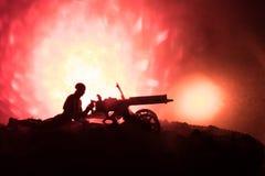 Άτομο με το πολυβόλο τη νύχτα, το υπόβαθρο έκρηξης πυρκαγιάς ή τις στρατιωτικές σκιαγραφίες που παλεύει τη σκηνή στο υπόβαθρο ουρ Στοκ φωτογραφίες με δικαίωμα ελεύθερης χρήσης