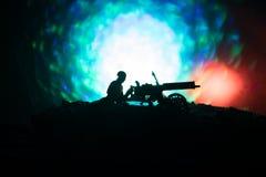 Άτομο με το πολυβόλο τη νύχτα, το υπόβαθρο έκρηξης πυρκαγιάς ή τις στρατιωτικές σκιαγραφίες που παλεύει τη σκηνή στο υπόβαθρο ουρ Στοκ φωτογραφία με δικαίωμα ελεύθερης χρήσης