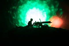 Άτομο με το πολυβόλο τη νύχτα, το υπόβαθρο έκρηξης πυρκαγιάς ή τις στρατιωτικές σκιαγραφίες που παλεύει τη σκηνή στο υπόβαθρο ουρ Στοκ εικόνα με δικαίωμα ελεύθερης χρήσης