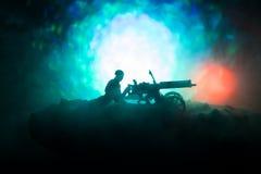 Άτομο με το πολυβόλο τη νύχτα, το υπόβαθρο έκρηξης πυρκαγιάς ή τις στρατιωτικές σκιαγραφίες που παλεύει τη σκηνή στο υπόβαθρο ουρ Στοκ Εικόνα