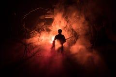 Άτομο με το ρεύμα ποταμού στο απόκοσμο δάσος τη νύχτα με το φως, ή πολεμική έννοια Στρατιωτικές σκιαγραφίες που παλεύουν τη σκηνή Στοκ εικόνα με δικαίωμα ελεύθερης χρήσης