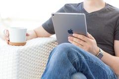 Άτομο με το ρολόι της Apple που κρατά το διαθέσιμο νέο iPad υπέρ Στοκ εικόνα με δικαίωμα ελεύθερης χρήσης