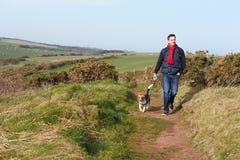 Άτομο με το σκυλί που περπατά κατά μήκος της παράκτιας πορείας στοκ εικόνες