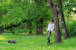 Άτομο με το σκυλί που περπατά στο δάσος Στοκ Εικόνες