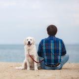 Άτομο με το σκυλί του στη συνεδρίαση θερινών παραλιών πίσω στη κάμερα Στοκ Εικόνες
