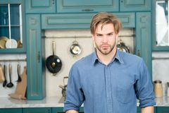 Άτομο με το σοβαρό πρόσωπο στην μπλε στάση πουκάμισων στην κουζίνα Στοκ φωτογραφία με δικαίωμα ελεύθερης χρήσης