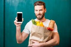Άτομο με το σύνολο τηλεφώνων και τσαντών των τροφίμων Στοκ εικόνες με δικαίωμα ελεύθερης χρήσης