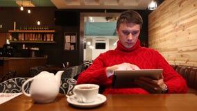 Άτομο με το τσάι κατανάλωσης υπολογιστών ταμπλετών στον καφέ απόθεμα βίντεο