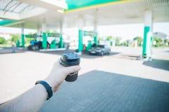 Άτομο με το φλυτζάνι καφέ που πηγαίνει στο αυτοκίνητό του στο βενζινάδικο Στοκ φωτογραφία με δικαίωμα ελεύθερης χρήσης