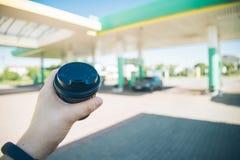 Άτομο με το φλυτζάνι καφέ που πηγαίνει στο αυτοκίνητό του στο βενζινάδικο Στοκ Φωτογραφίες