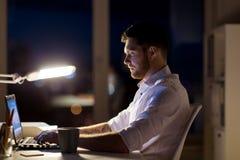 Άτομο με το lap-top και καφές που λειτουργεί τη νύχτα το γραφείο Στοκ εικόνα με δικαίωμα ελεύθερης χρήσης