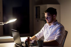Άτομο με το lap-top και καφές που λειτουργεί τη νύχτα το γραφείο Στοκ Εικόνα