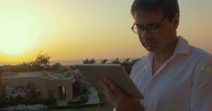 Άτομο με το PC ταμπλετών στο ηλιοβασίλεμα απόθεμα βίντεο