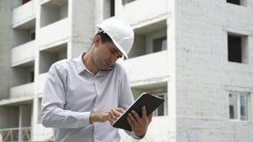Άτομο μηχανικών με την ταμπλέτα που μιλά στο κινητό τηλέφωνο και που ελέγχει τη διαδικασία τεχνολογίας κτηρίου απόθεμα βίντεο