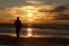 Άτομο μπροστά από το ηλιοβασίλεμα θάλασσας Στοκ Φωτογραφία