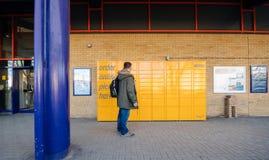 Άτομο μπροστά από το ντουλάπι του Αμαζονίου στο σταθμό τρένου της Οξφόρδης receiv Στοκ Εικόνες