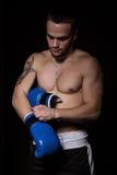 Άτομο μπόξερ που βάζει στα μπλε εγκιβωτίζοντας γάντια Στοκ Εικόνες