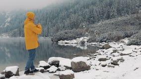 Άτομο οδοιπόρων που φυσά σε ετοιμότητα, κρύος καιρός Νέος ταξιδιώτης που στέκεται στα χιονώδη βουνά κοντά στην όμορφη λίμνη απόθεμα βίντεο