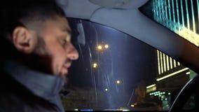 Άτομο πίσω από τη ρόδα μιας οδήγησης αυτοκινήτων στις οδούς βραδιού φιλμ μικρού μήκους