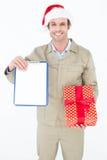 Άτομο παράδοσης στην περιοχή αποκομμάτων και το δώρο εκμετάλλευσης καπέλων Santa Στοκ εικόνα με δικαίωμα ελεύθερης χρήσης