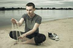 άτομο παραλιών που κάθεται τις στοχαστικές νεολαίες Στοκ Φωτογραφίες