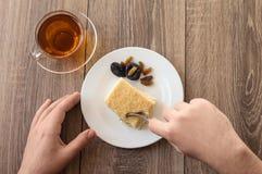 Άτομο που έχει ένα φλυτζάνι του τσαγιού με ένα κέικ Στοκ Φωτογραφία