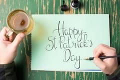 Άτομο που έχει μια μπύρα με την ευτυχή κάρτα ημέρας του ST Πάτρικ Στοκ Εικόνες
