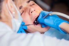 Άτομο που έχει τα δόντια εξετασμένων στους οδοντιάτρους οδοντικούς Στοκ Εικόνα