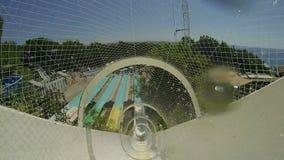 Άτομο που έχει τη διασκέδαση, που γλιστρά στο πάρκο νερού φιλμ μικρού μήκους