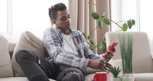 Άτομο που έχει τον καφέ προσέχοντας τη TV και χρησιμοποιώντας το κινητό τηλέφωνο στο σπίτι απόθεμα βίντεο