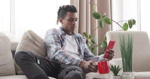 Άτομο που έχει τον καφέ χρησιμοποιώντας το κινητό τηλέφωνο στον καναπέ φιλμ μικρού μήκους