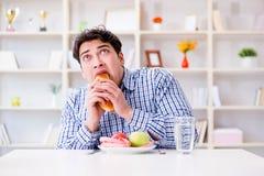 Άτομο που έχει το δίλημμα μεταξύ των υγιών τροφίμων και του ψωμιού να κάνει δίαιτα con Στοκ Εικόνες
