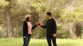 Άτομο που δίνει μια μορφή καρδιών στη φίλη του στο πάρκο φιλμ μικρού μήκους