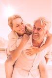 Άτομο που δίνει στη χαμογελώντας σύζυγό του ένα σηκώνω στην πλάτη στην παραλία Στοκ Φωτογραφία