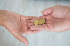 Άτομο που δίνει τα νομίσματα σε ένα άλλο πρόσωπο Στοκ εικόνα με δικαίωμα ελεύθερης χρήσης